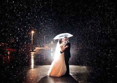 bride and groom umbrella in rain