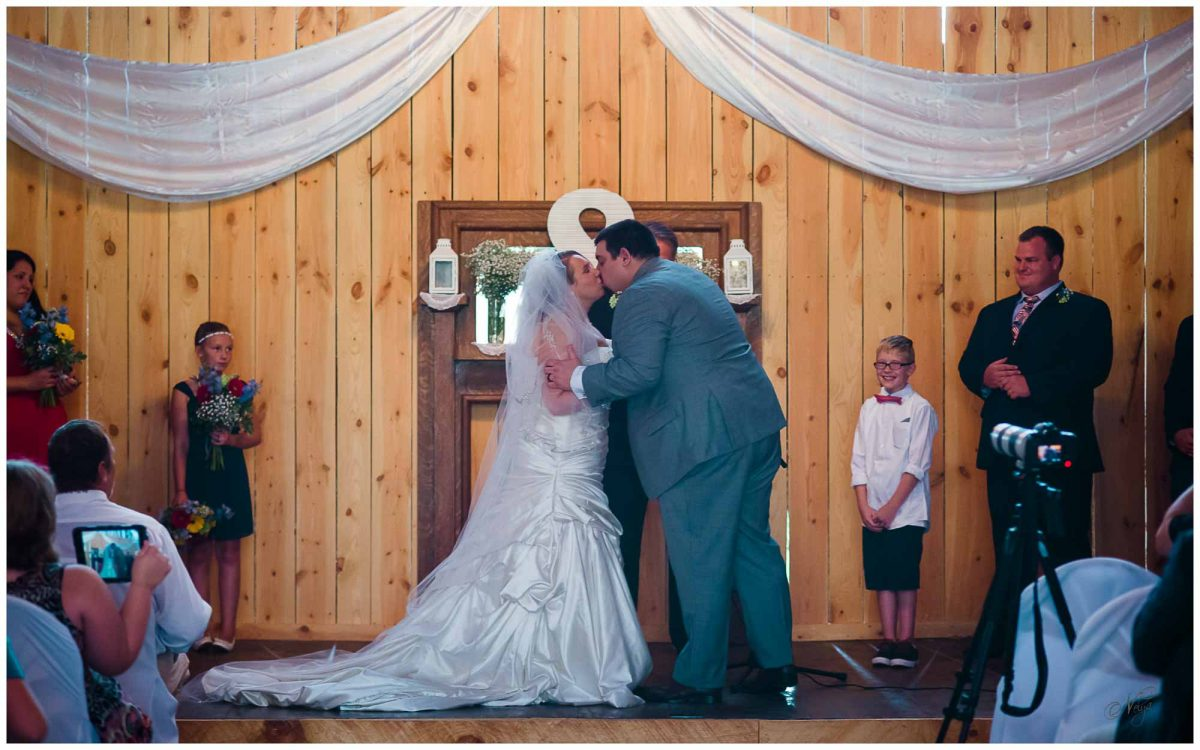 groom kissing his bride at wedding ceremony inside Stinnett Farm barn
