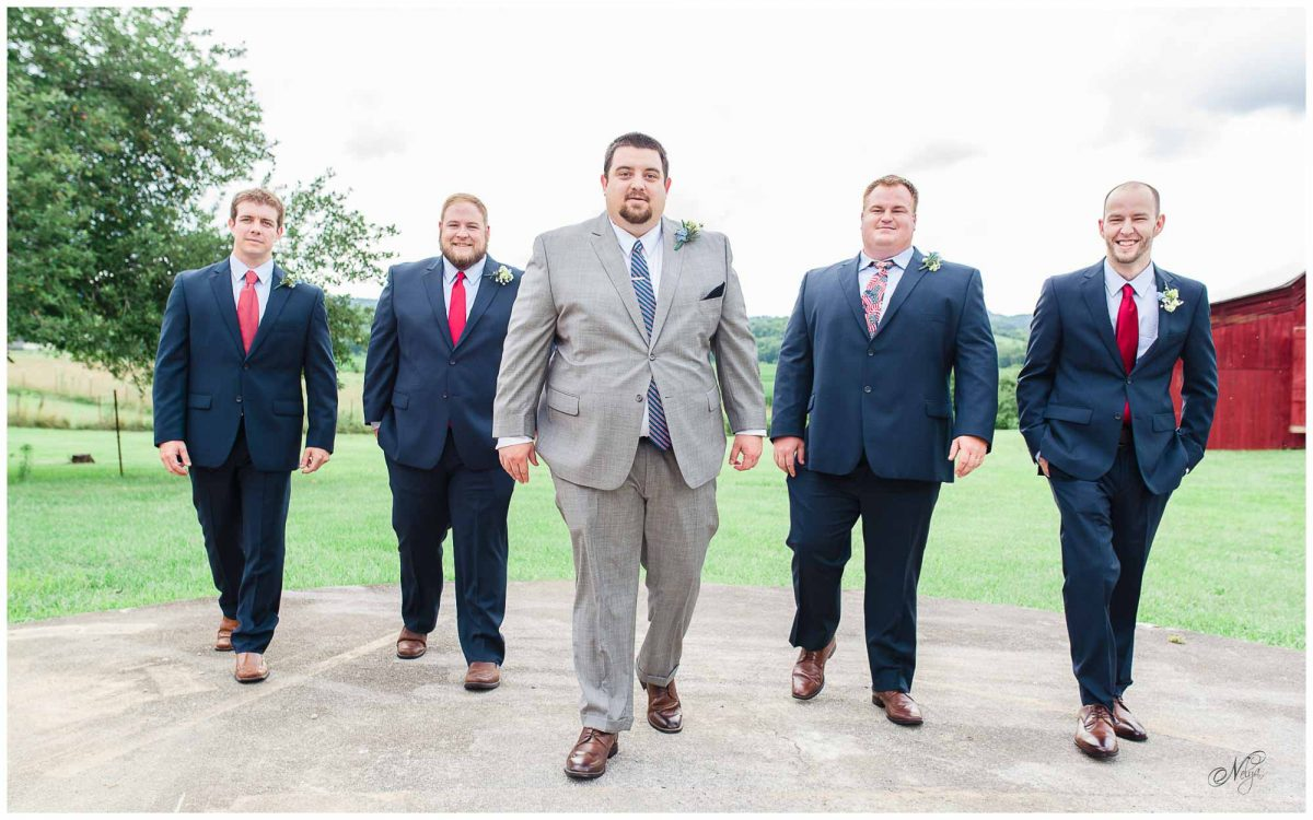 groom and groomsmen walking in front of Stinnett Barn