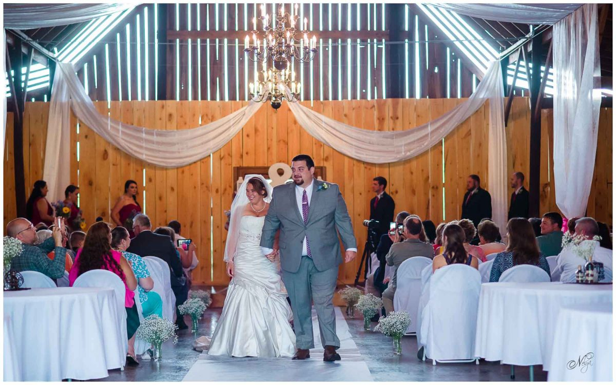 new mr and mrs walking down aisle at Stinnett Farm wedding