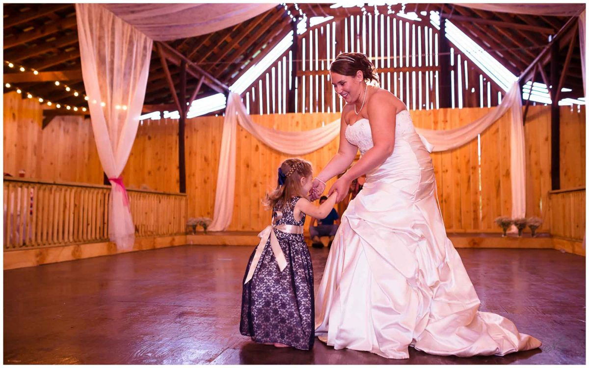 bride and flower girl dancing at Stinnett Farm