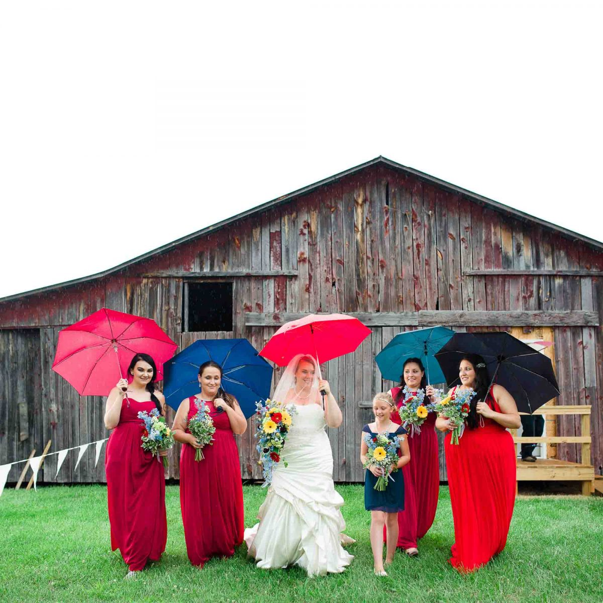 bride and bridesmaids under umbrellas in the rain at Stinnett Farm in Rogersville
