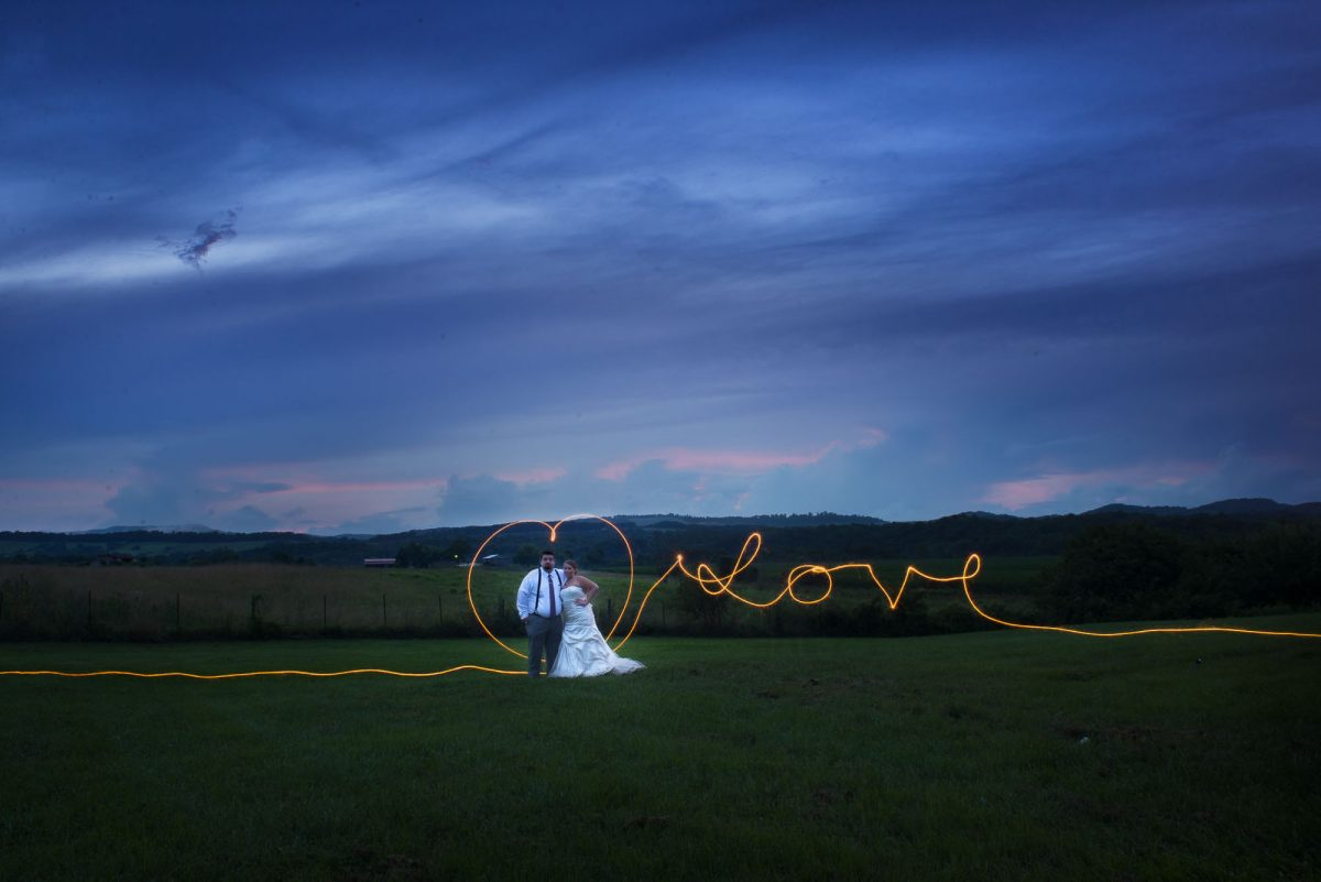 bride and groom with Love written with sparkles at Stinnett Farm wedding venue in Rogersville TN