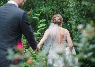 bride leading groom through garden at Rockwood manor on VA