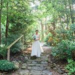 bride walking down stone steps to forest wedding