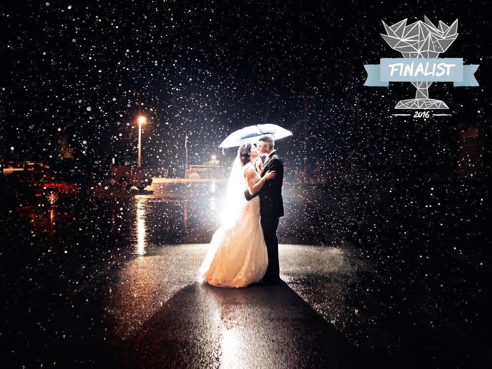 wedding couple under umbrella in rain