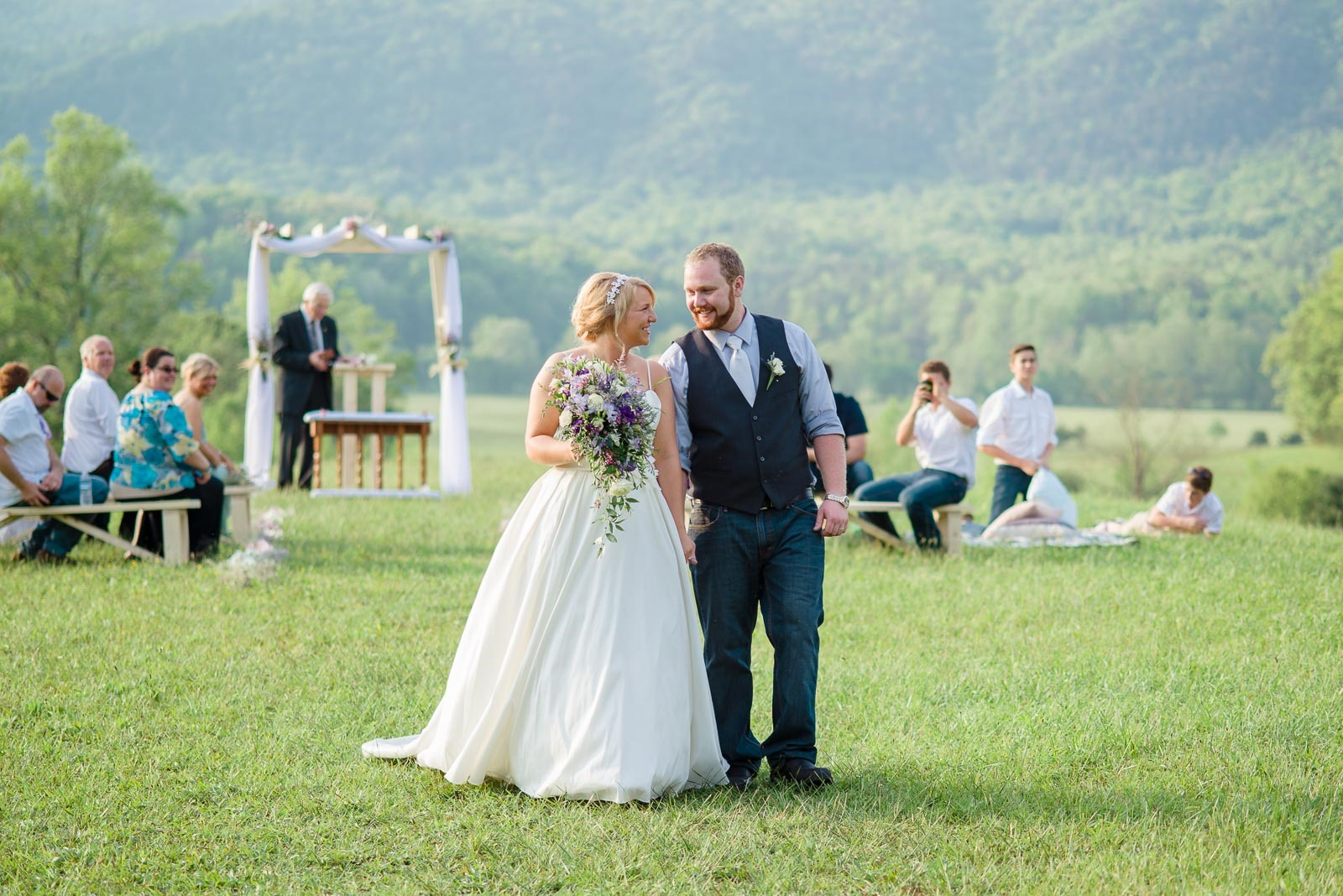Bride with purple waterfalls bouquet and groom with navy vest and light blue shirt at cades cove wedding in the mountains