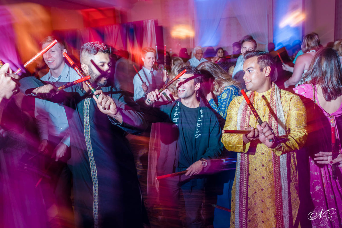 guys dancing with dandia sticks at an Indian wedding at Griffin Gate Marriott