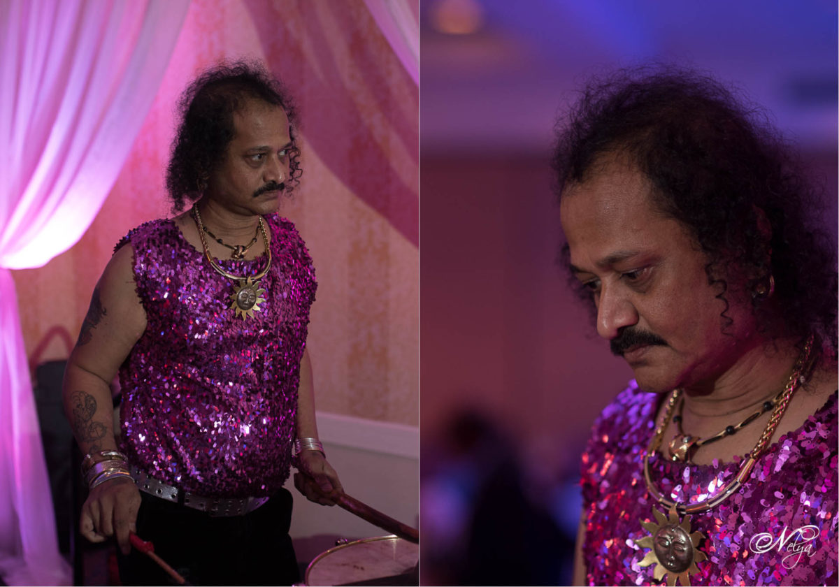 traditional Indian drummer playing at the sangeet wore a pink sequined shirt