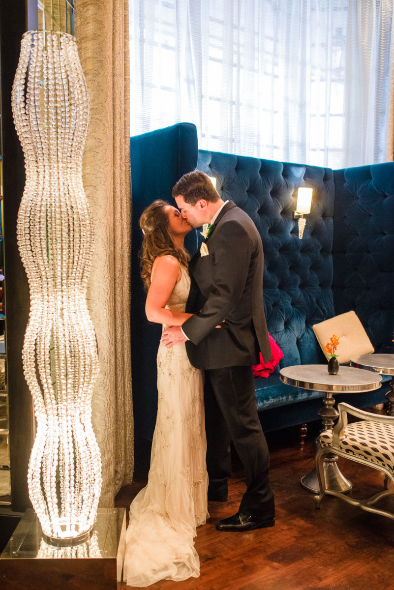 Bride and groom share a kiss in Ritz Carlton Atlanta lobby