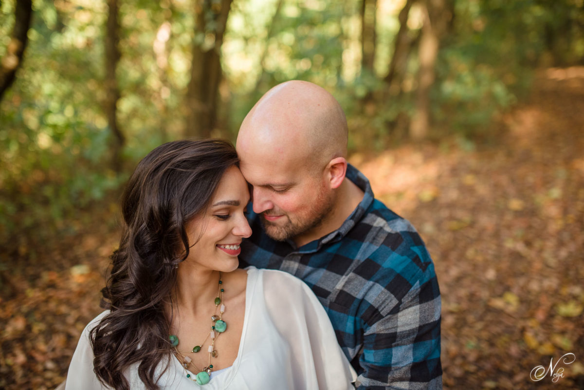 engagement photo of couple posed on cedar stump at Hiwassee River Weddings and Events in Delano TN