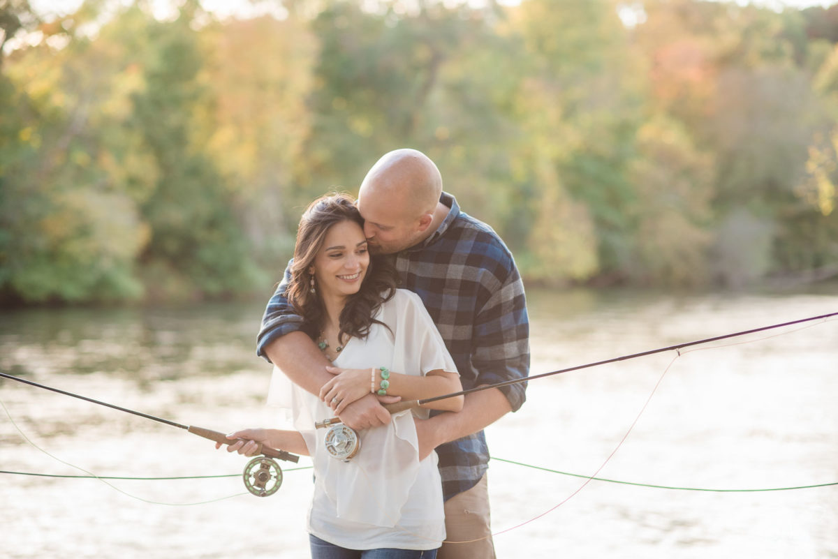 couple hugging with fly fishing rods at Hiwassee River Weddings
