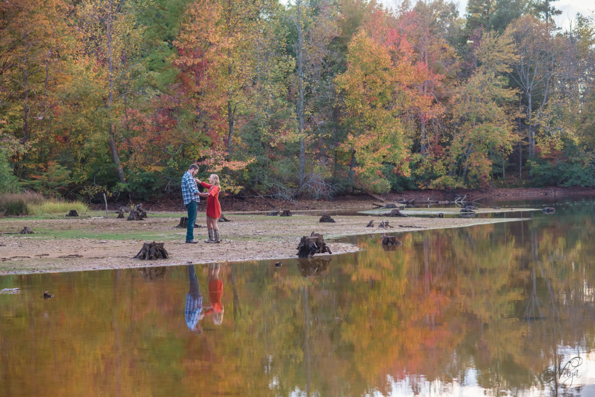 engaged couple and fall foliage reflecting in indian boundary lake