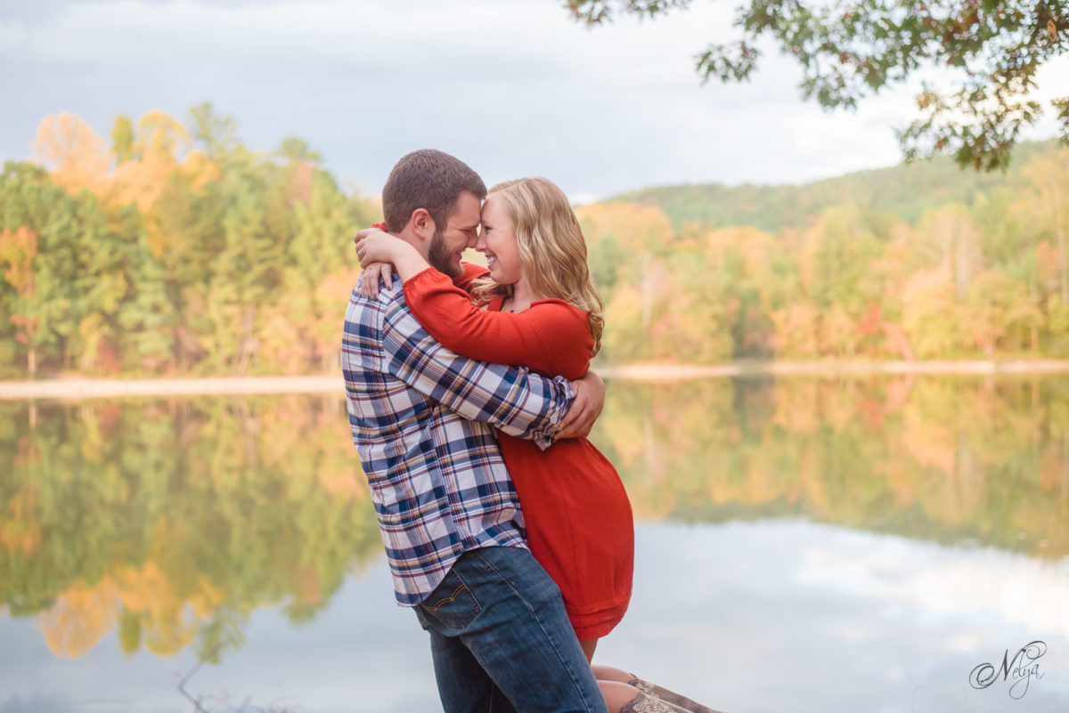 couple at edge of Indian Boundary lake with fall colors behind