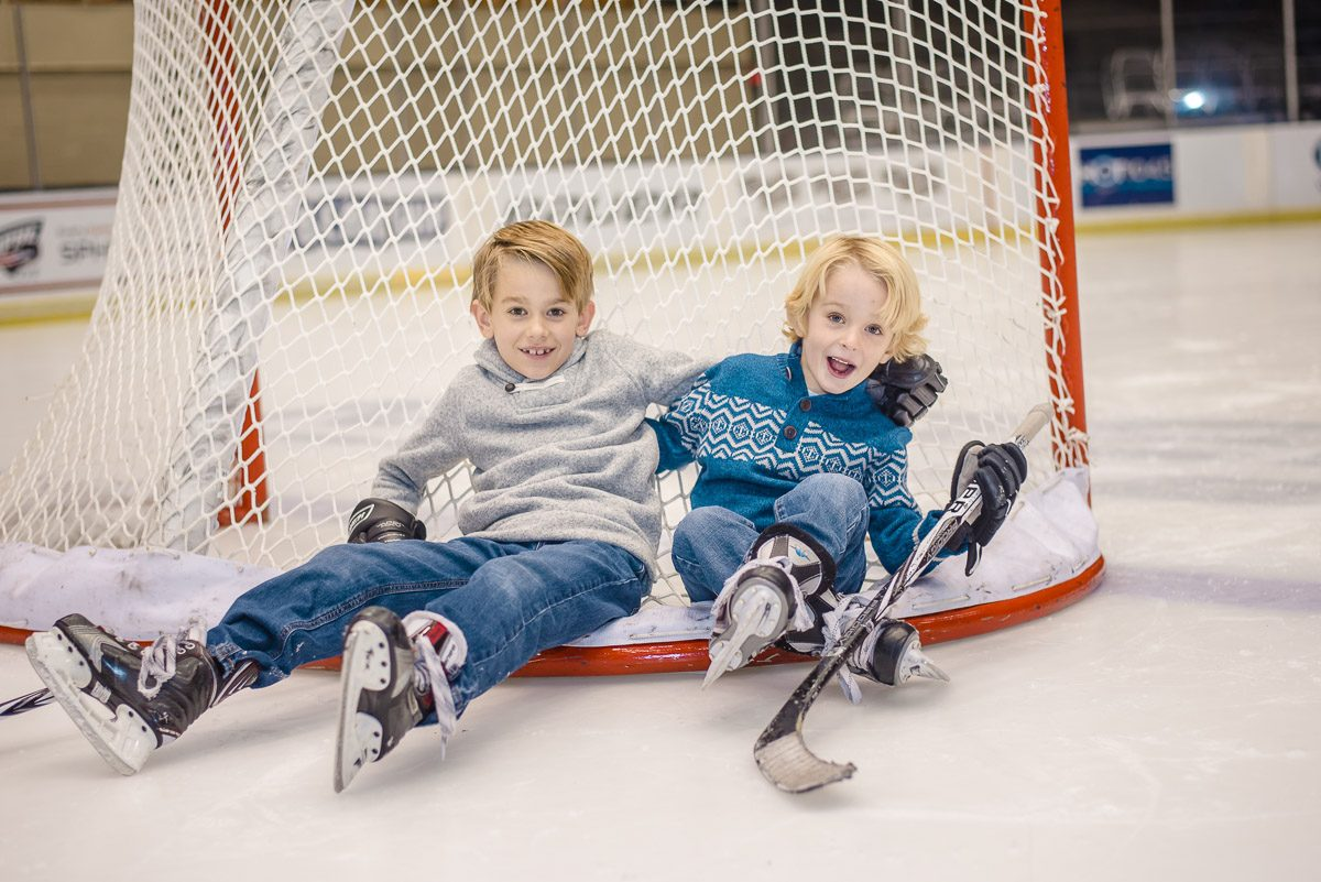 brothers sitting on the back of a hockey net at civic coliseum in Knoxville