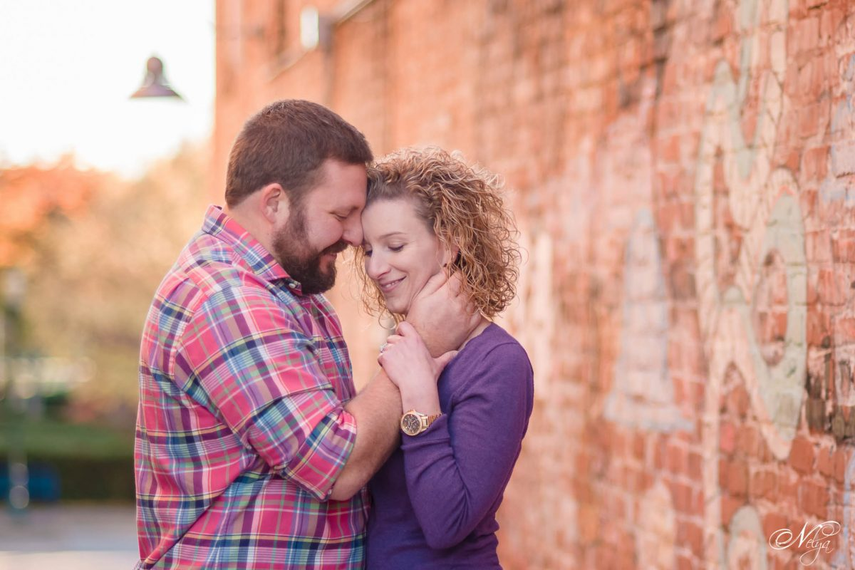 couple by brick wall at Coolidge park Chattanooga for Engagement photos