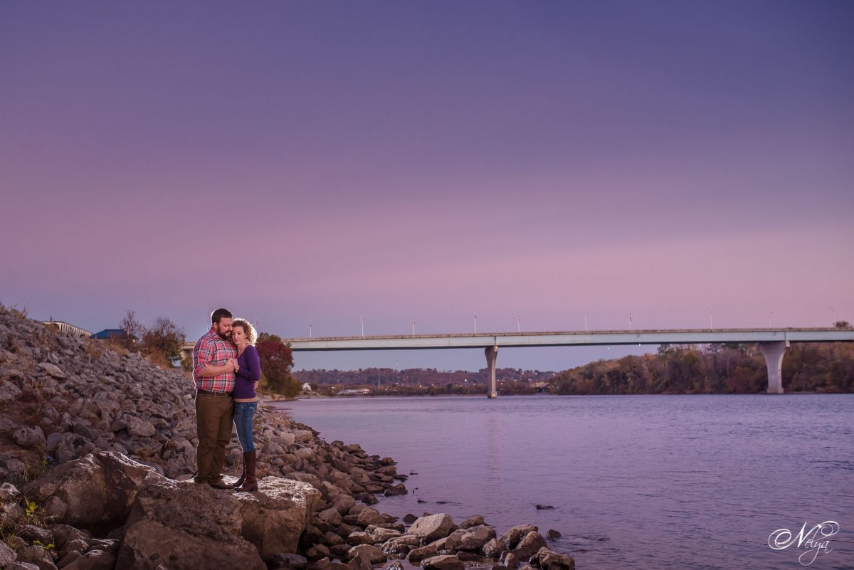 Couple standing on rocks for purple sky sunset at edge of Tennessee River in Coolidge Park Chattanooga