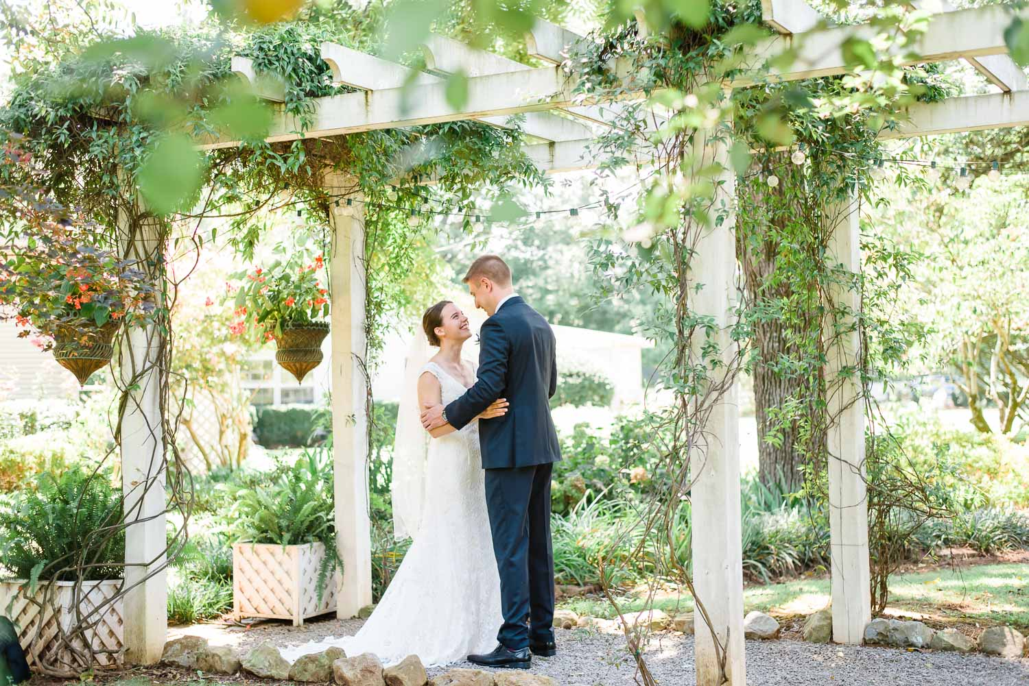 bride and groom talking under garden arbor at Creekside Plantation venue in Huntsville AL