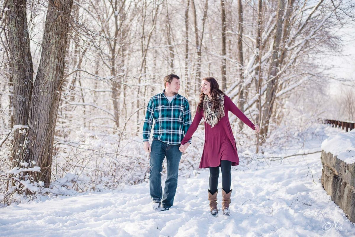 couple walking and laughing in snow at an overlook on the cherohala skyway tellico plains
