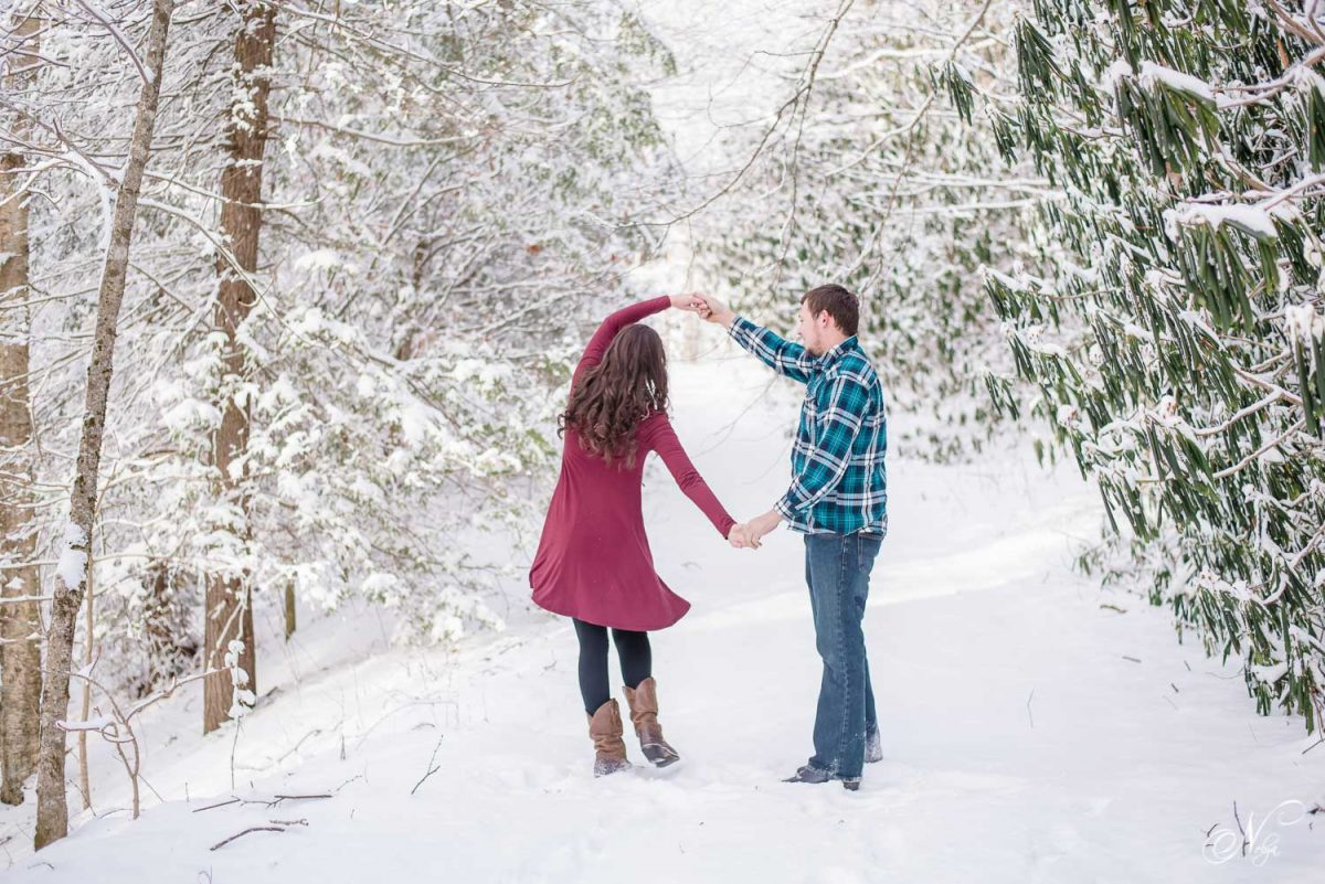 Girl in red dress and guy dancing in the snow in Tellico Plains