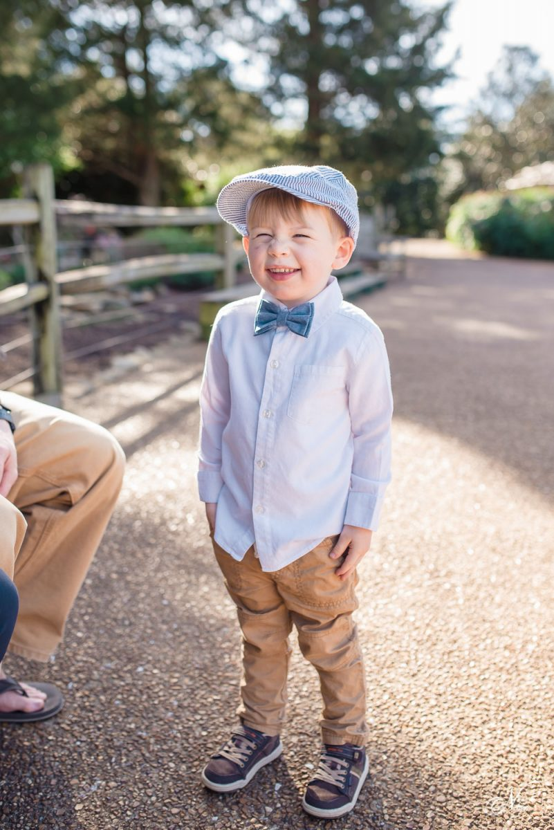 smiling toddler in bowtie hat and skinny jeans