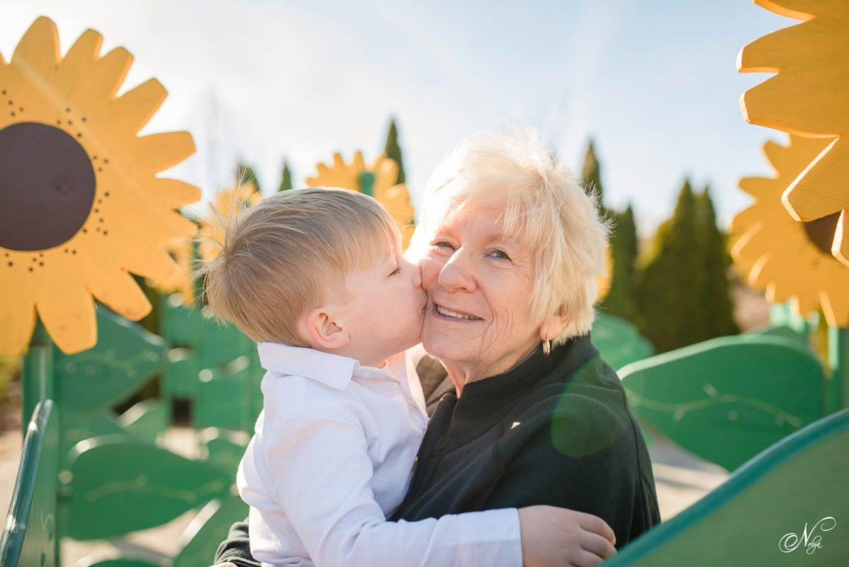 boy kiss his Grandmother in sunflowers