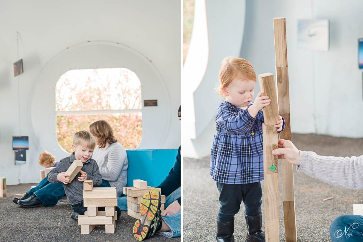 toddler girl in plaid shirt and leggings and boy playing with blocks