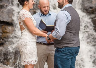 bride in short lace dress. Elopement at waterfalls