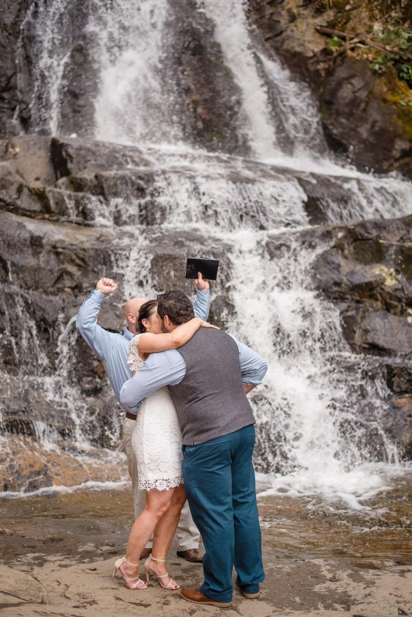 bride kissing groom in fron of waterfalls