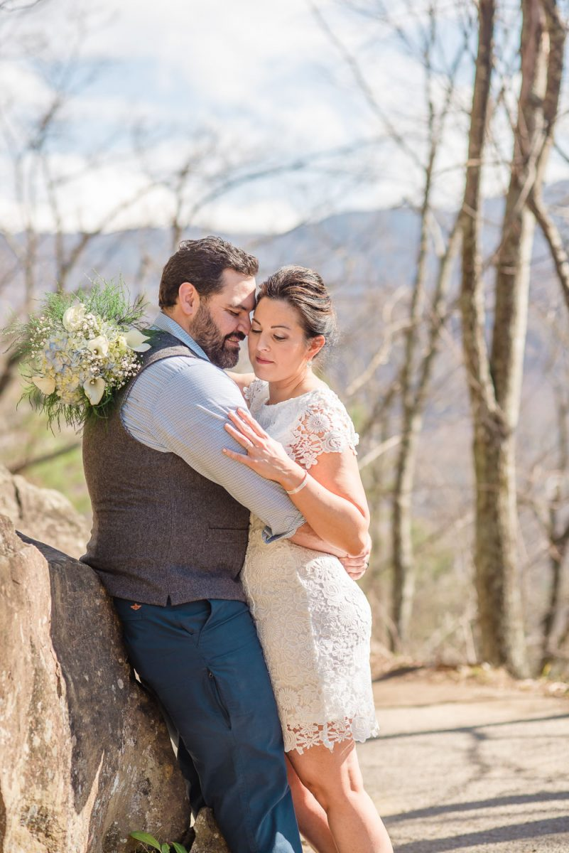 groom and bride leaning on rock in TN at waterfalls elopement