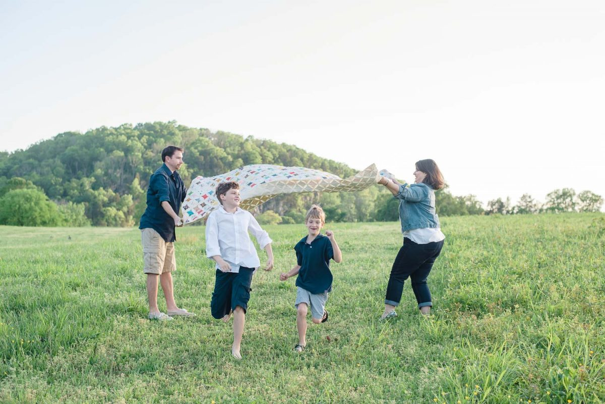 kids running under quilt for fun family photos