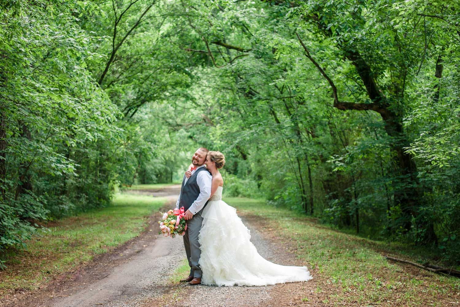 bride and groom on tree covered road