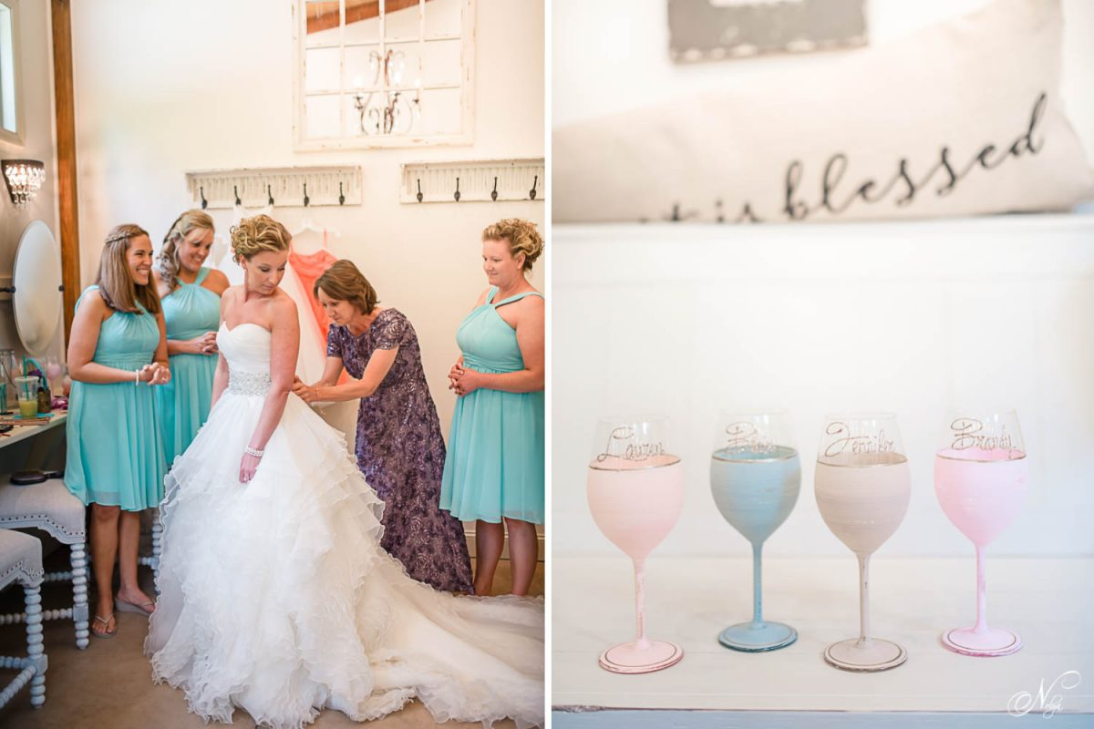 mom buttoning brides dress at wedding venue and painted wine glasses