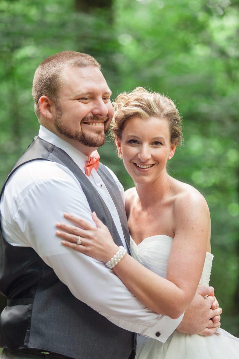 bride smiling at camera groom just beaming at the world