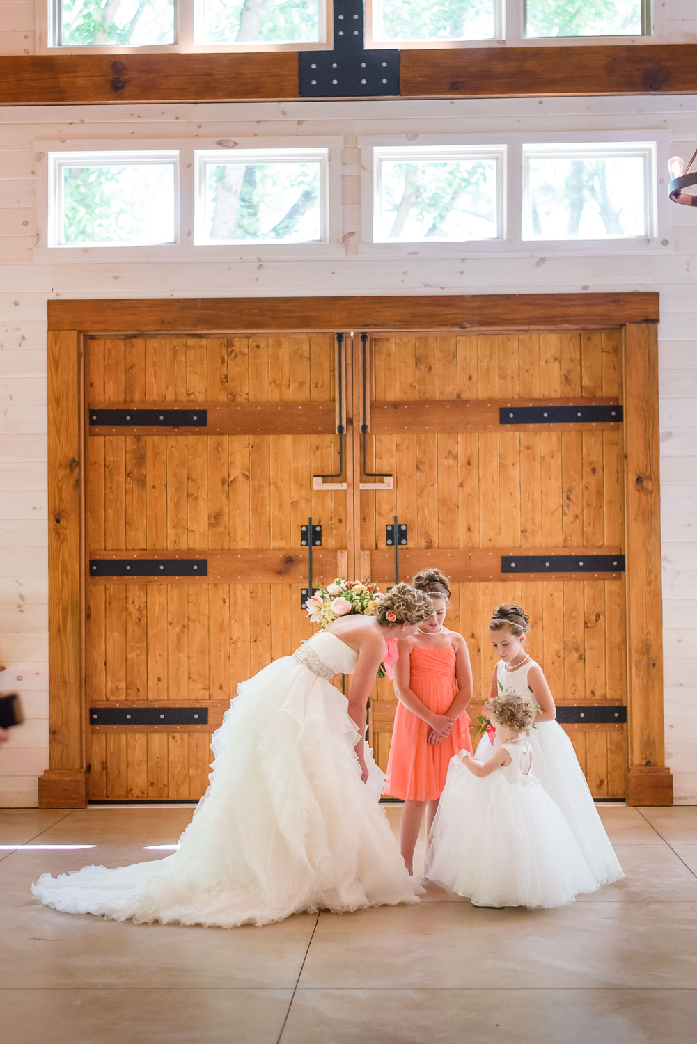 flower girls admiring bride's dress in front of big wooden door