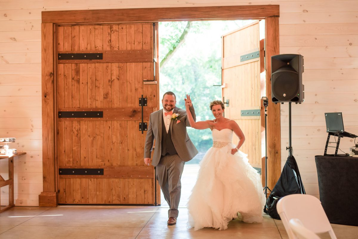 grand entrance ofbride and groom through big wooden doors