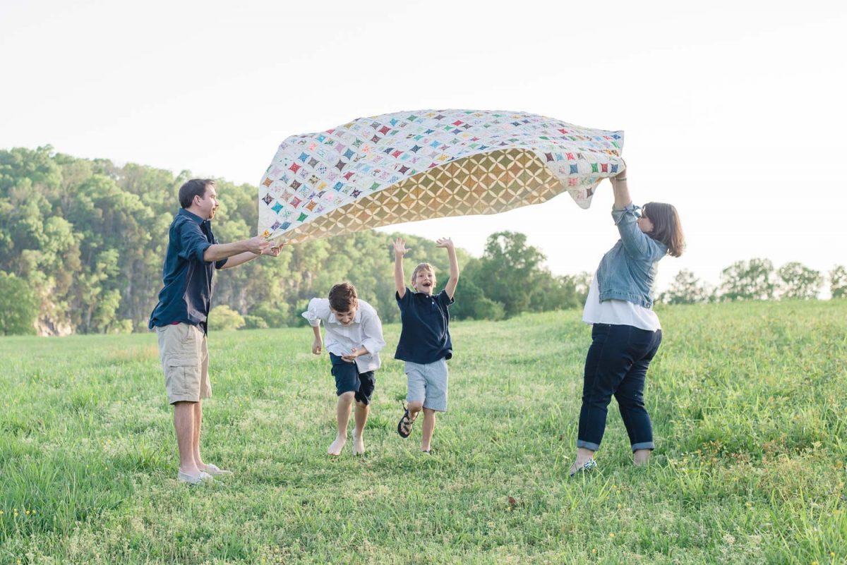 kids running under Grandma's quilt at park