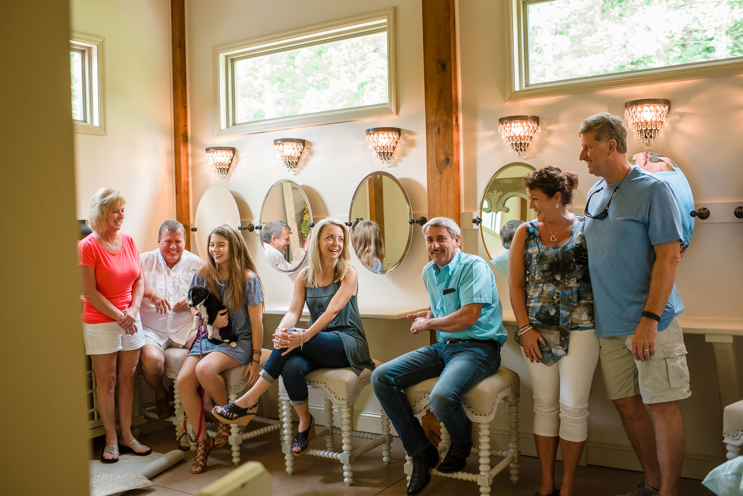 7 people sitting on white stools in bridal suite