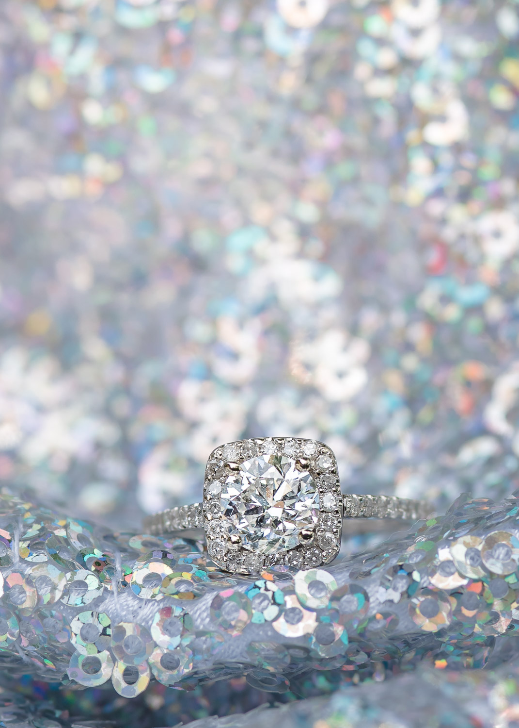 engagement ring sitting on sequins