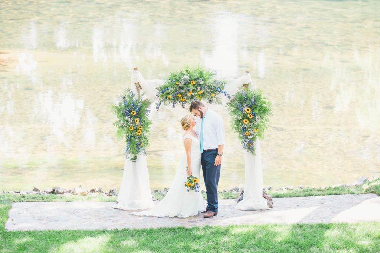 bride and groom under sunflower arch