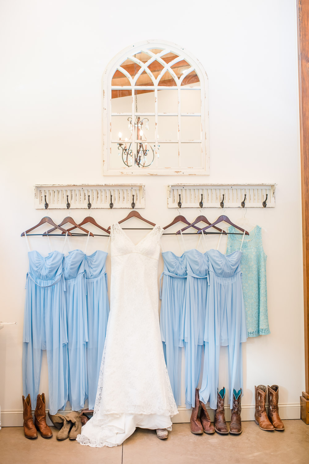 ice blue bridesmaids dresses and lace wedding dress hung on wall