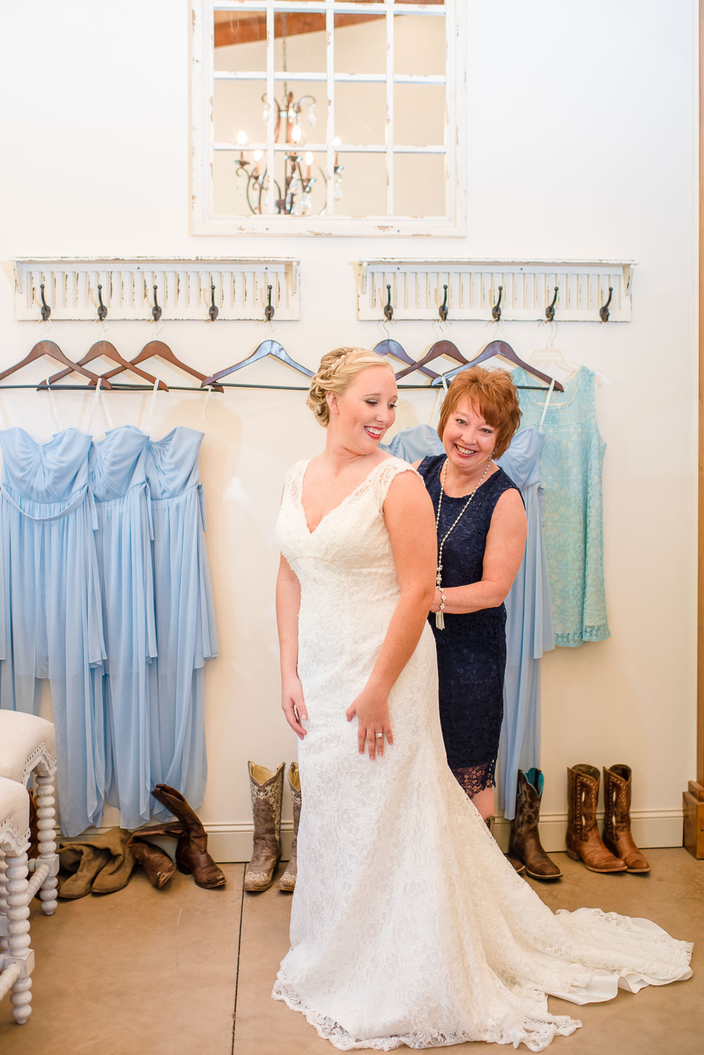 mother of the bride zipping bride's dress