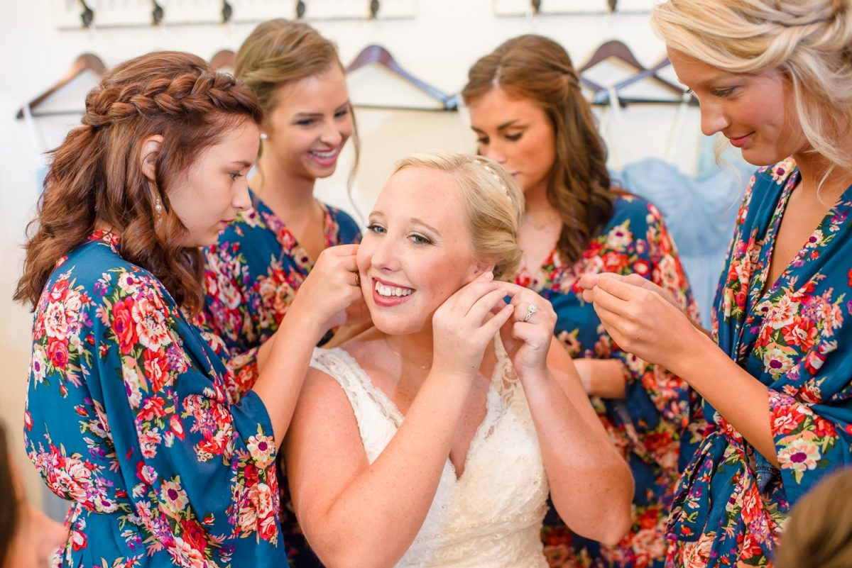 bride putting on earrings with help from bridesmaids in blue floral robes