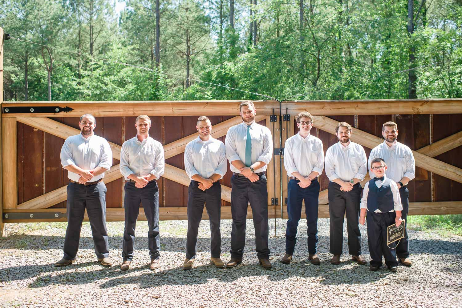 groomsmen in front of sawmill shed gate at Hiwassee River Weddings