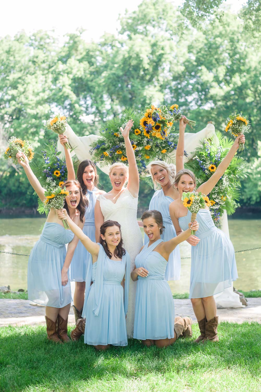 bride and bridesmaids in ice blue short dresses with sunflower bouquets