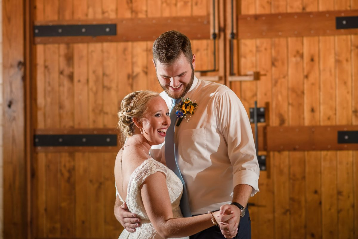 bride in lace dress and groom with sunflower boutonniere