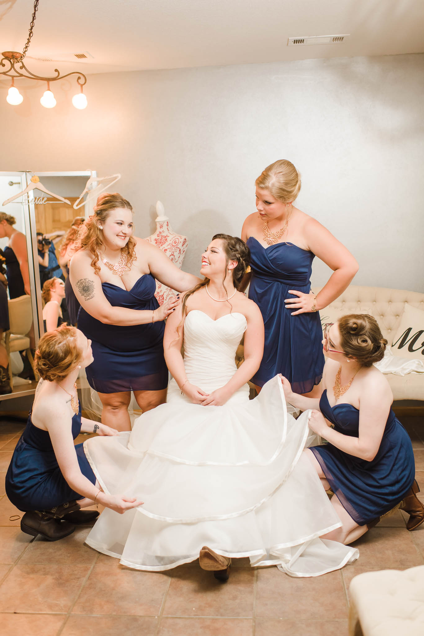 bridesmaids adjusting bride's dress on wedding day