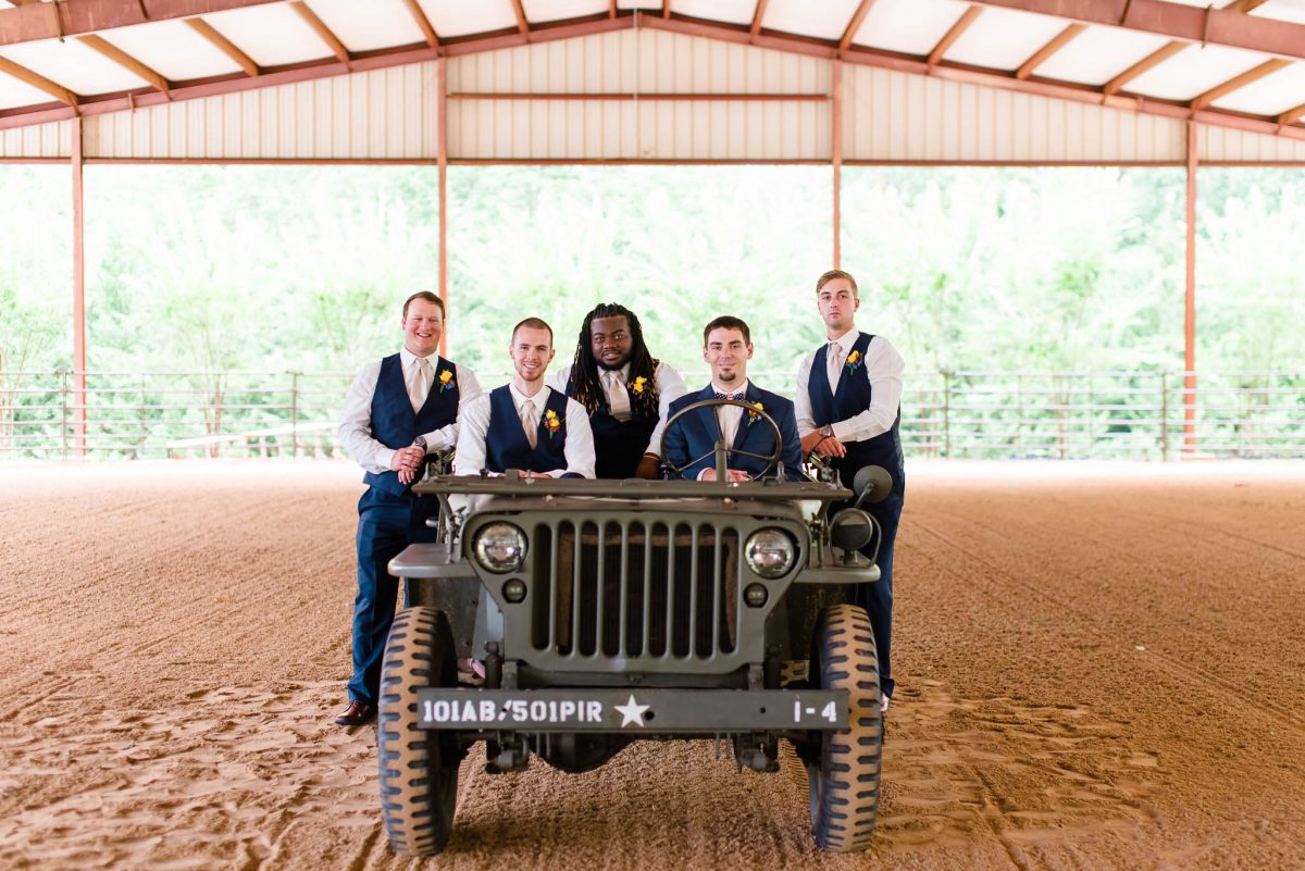 groom and groomsmen posed on WWII jeep at sundance farm in knoxville TN