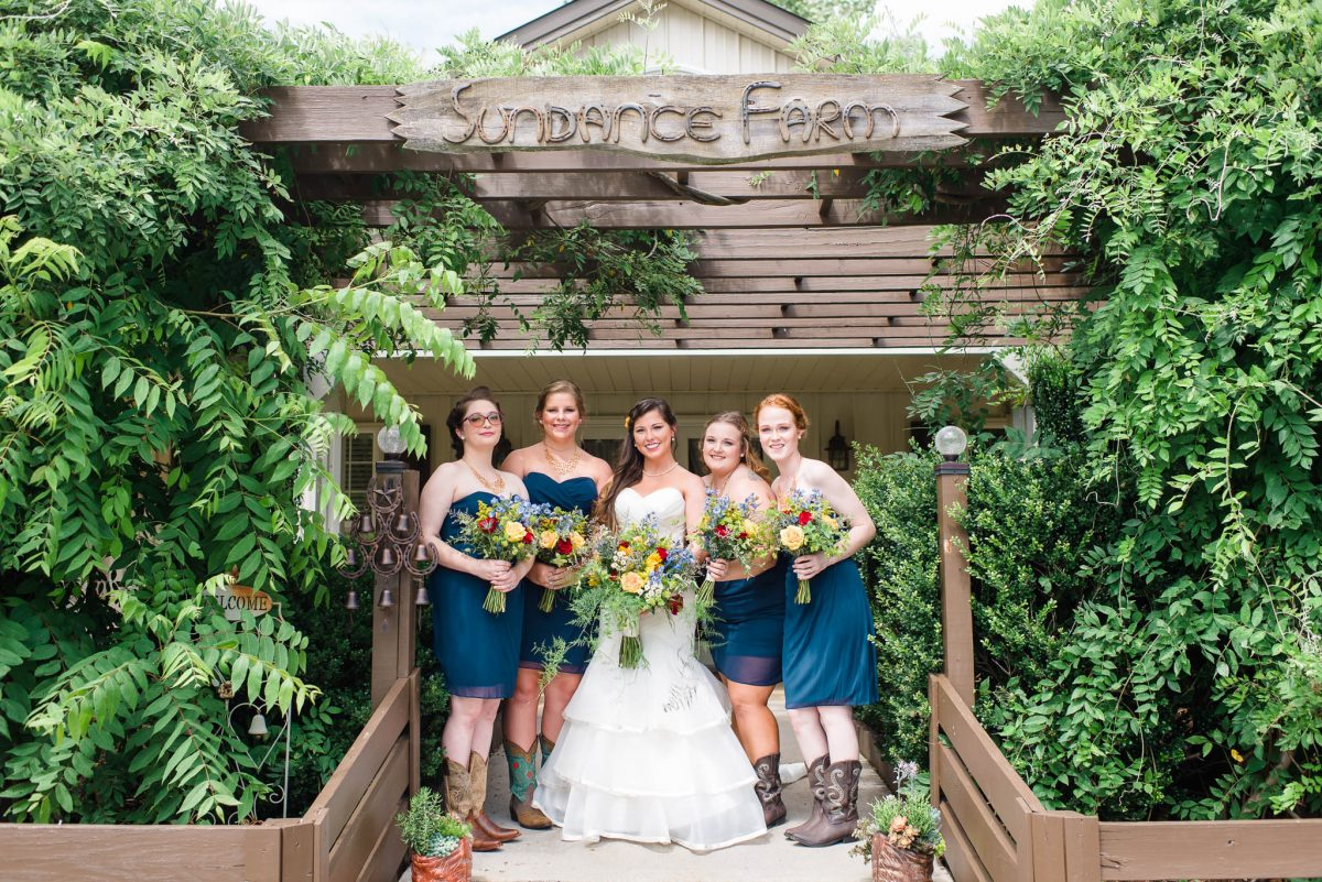 bride annd bridesmaids in navy with red yellow and blue bouquets