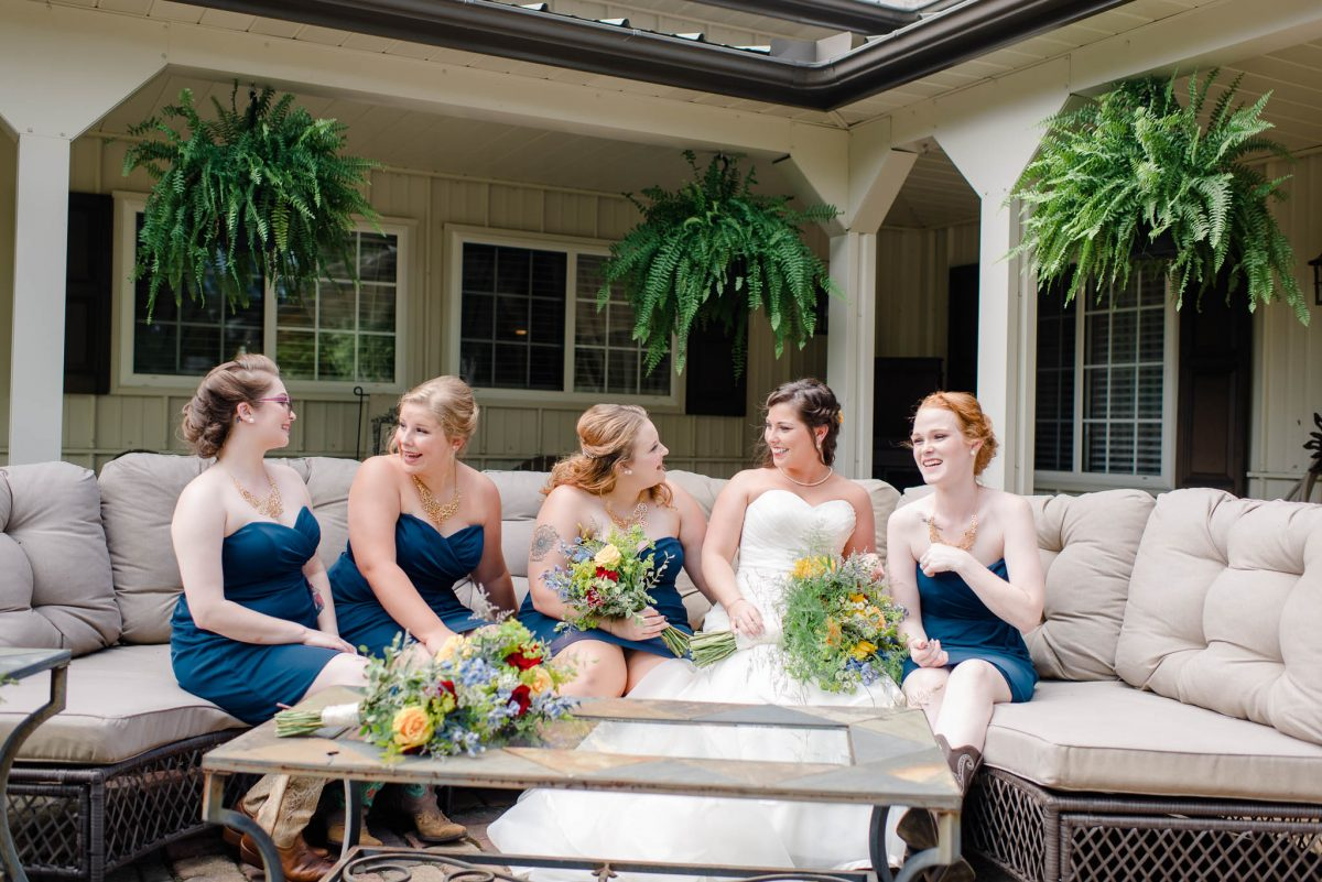 bride and girls sitting on couch outside at Sun dance farm in Knoxville
